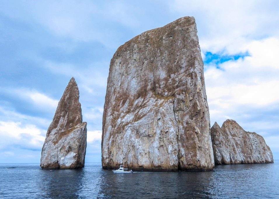 Kicker Rock, a massive rock formation, dwarfs a passing boat