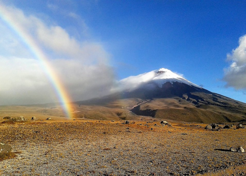 Two beautiful sights: a rainbow and Cotopaxi volcano