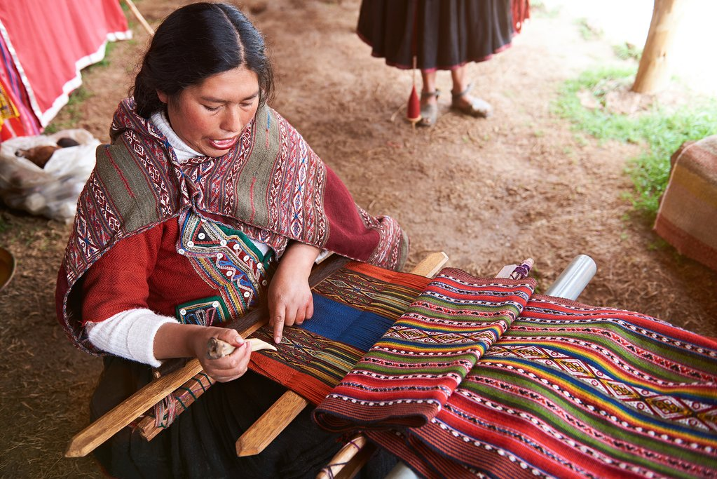 A Peruvian woman weaving on a traditional handloom