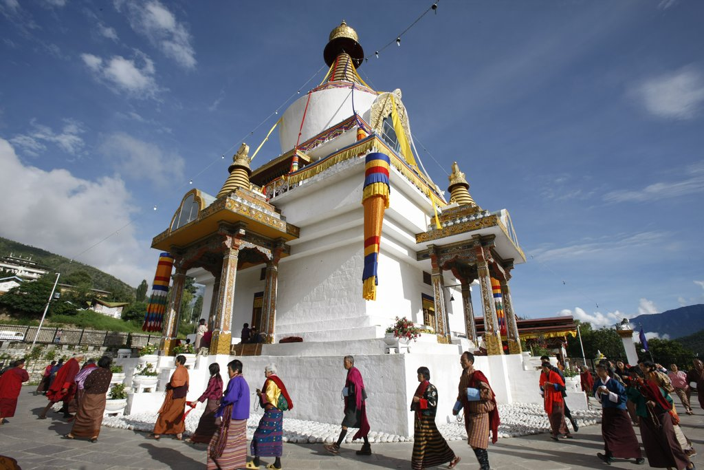 A steady stream of eldery people walk in a circular procession around the chorten