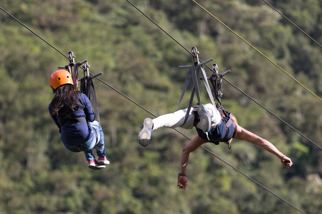Sliding down a tandem zip line one of many adventures you can have near the city of Baños.