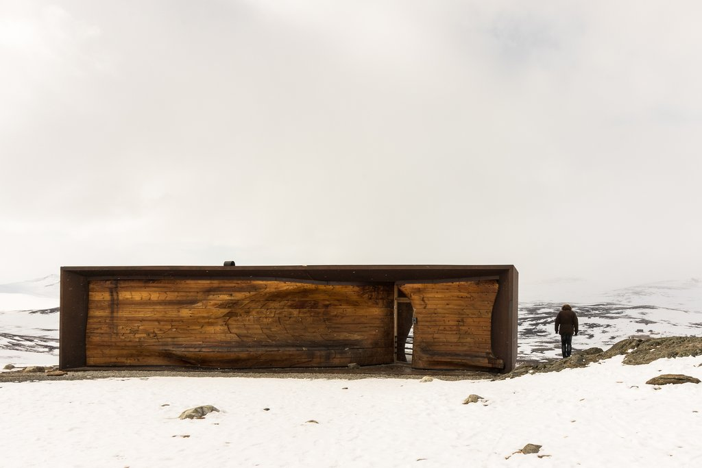 wooden, boxy lodge with lone figure in a frozen landscape