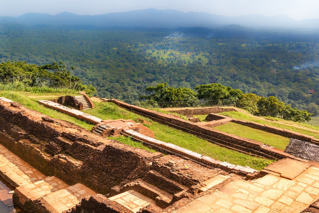 From the top of Sigiriya Rock Fortress, enjoy a view of the surrounding hills and elegantly terraced fortress floor