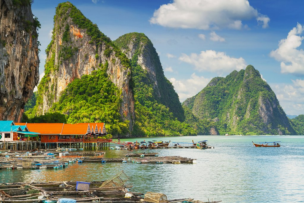 A small village sits beneath the dramatic limestone karsts in Phang Nga Bay.