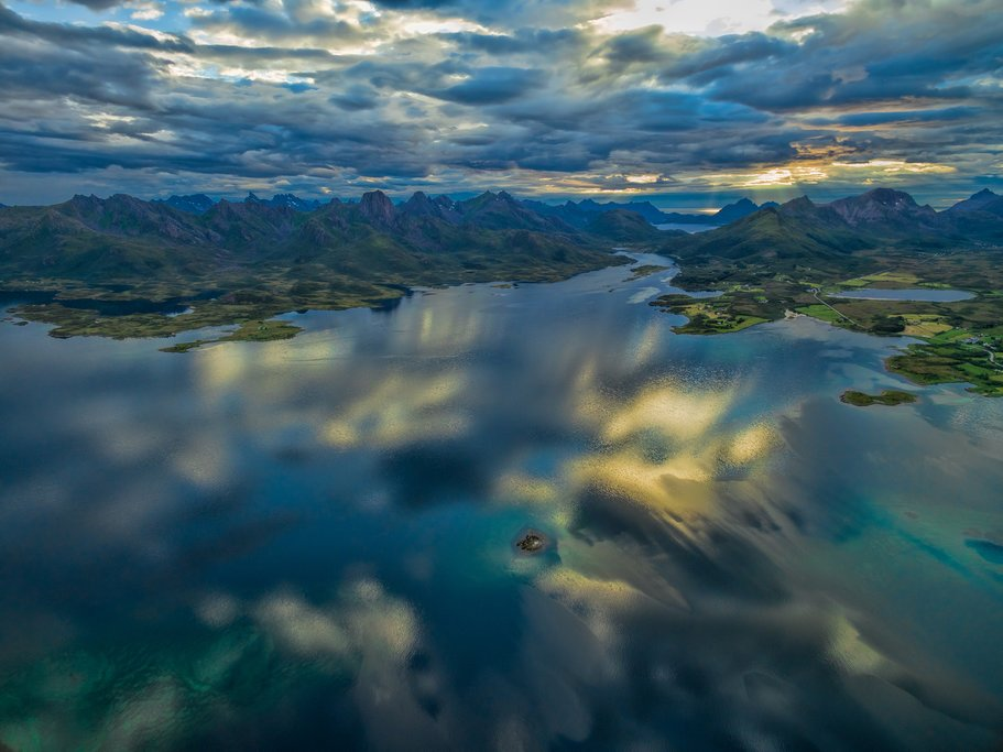 Scenic aerial view of reflecting clouds on Vesteralen islands with their dramatic mountain peaks