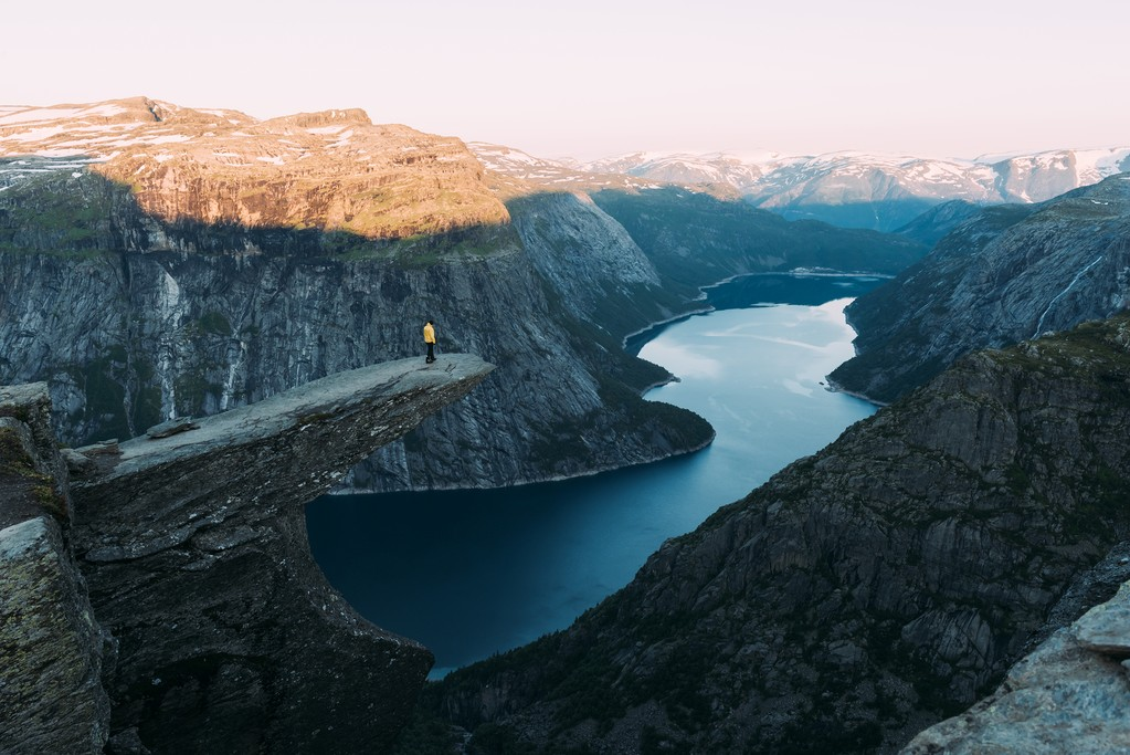 Alone tourist on Trolltunga rock - most spectacular and famous scenic cliff in Norway. Landscape photography in norwegian mountains