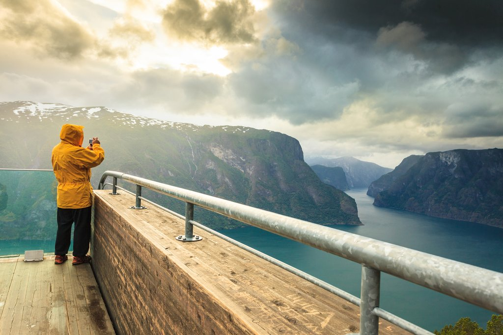 Male tourist nature photographer taking photo with camera enjoying Aurland fjord landscape from Stegastein lookout Norway Scandinavia.