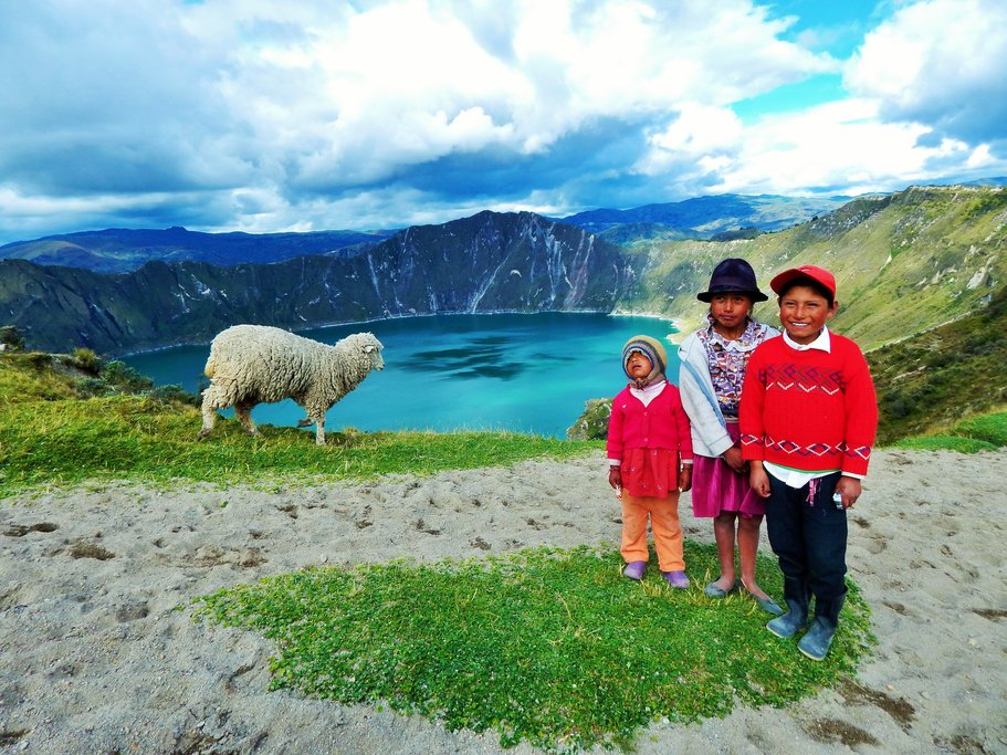 Local kids stop for a photo in front of the piercing blue water of Quilotoa Lake