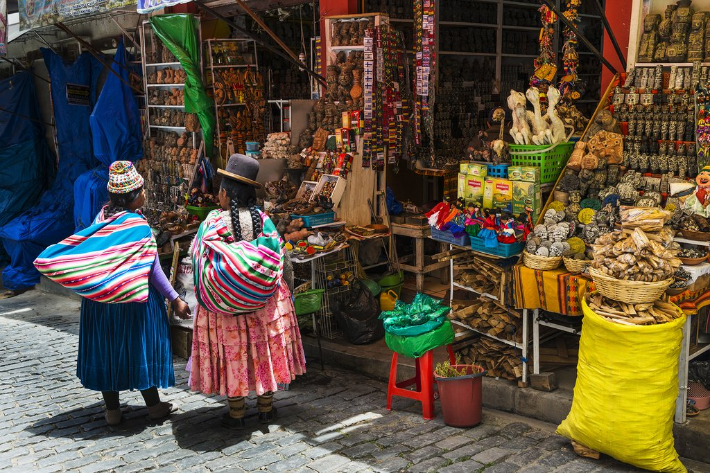 wo local woman wearing traditional clothing in front of a store in a street of the city of La Paz in Bolivia