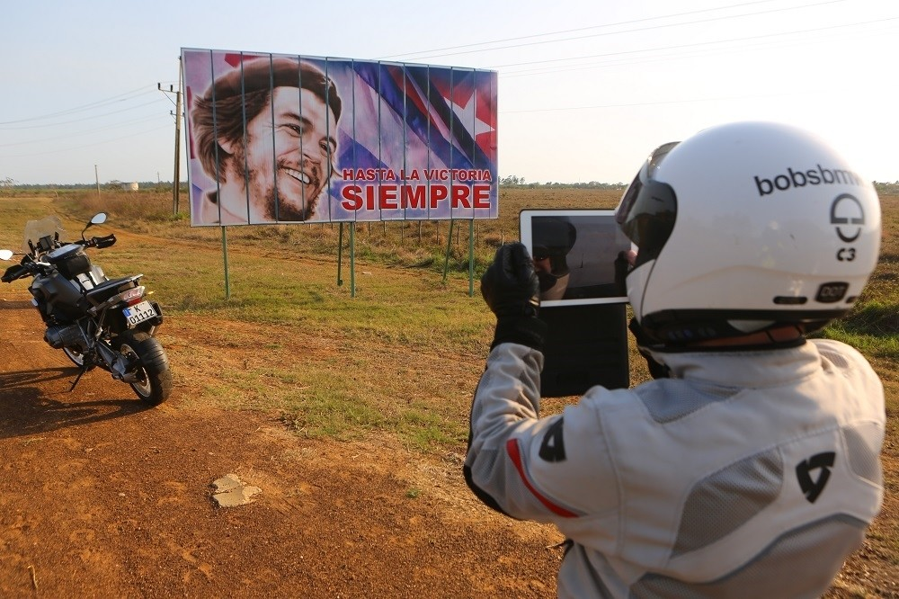 US motorcycle tour member photographs a Che Guevara billboard, Cuba; ; copyright Christopher P Baker. All rights reserved.