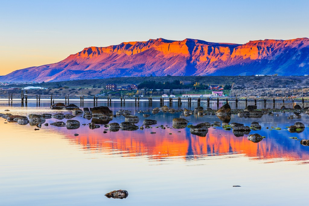 A gorgeous sunset reflects off the cliffs and water at Puerto Natales