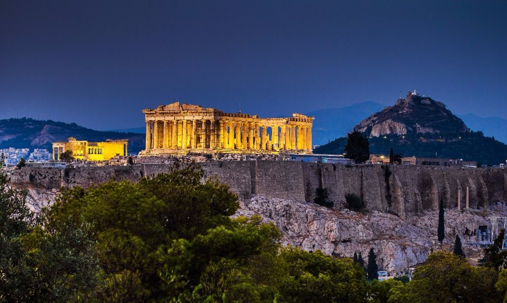 The Acropolis, lit up at night, makes a stunning contrast to the dark sky behind it