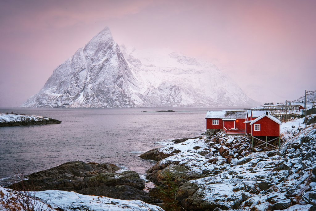 Famous tourist attraction Hamnoy fishing village on Lofoten Islands, Norway with red rorbu houses. With falling snow in winter on sunrise