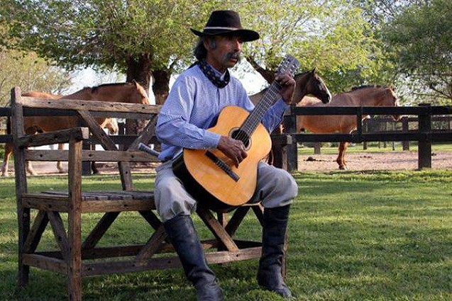 An Argentine gaucho strumming a tune on his guitar.