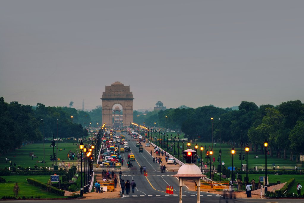 Foot and automobile traffic on the road leading up to the India Gate in Delhi in the evening