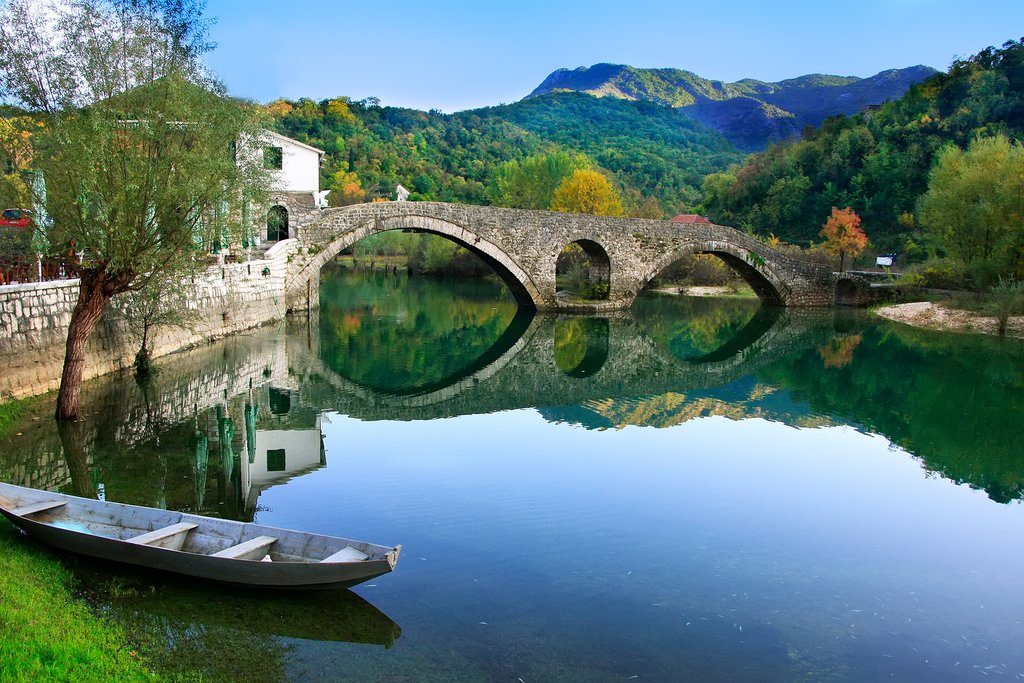 A stone-arched bridge reflected in the Crnojevića river in Montenegro