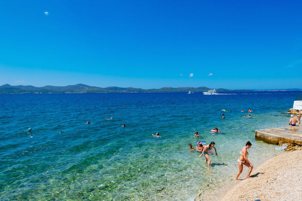 Beachgoers wade in the crystalline waters of the Adriatic Sea near Zadar
