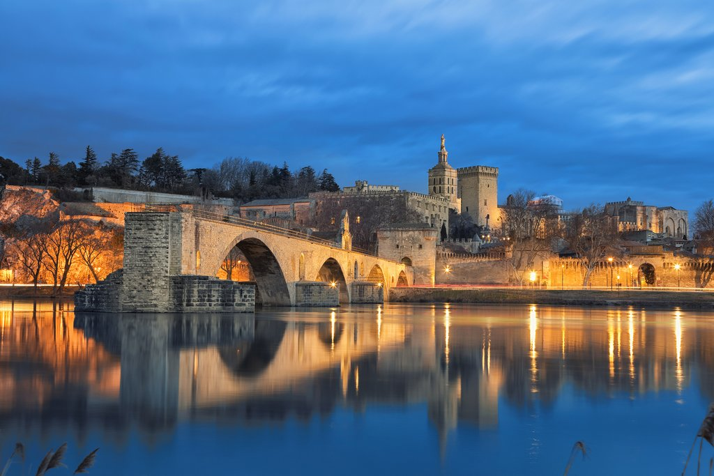 Historic Avignon's Palais des Papes and Pont Saint-Bénézet glow serenely in the early evening