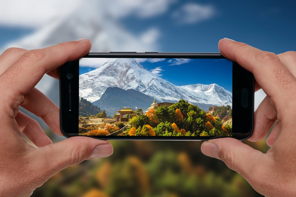 A tourist taking a photo of Manaslu and a Buddhist monastery