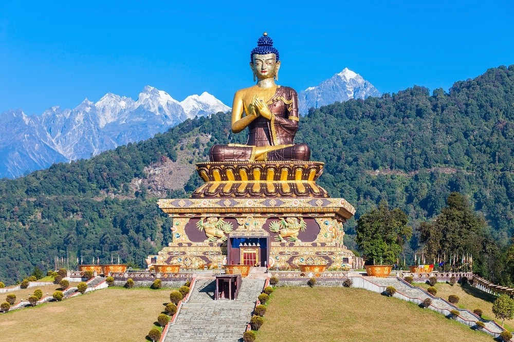Monastery statue in front of the Himalayas