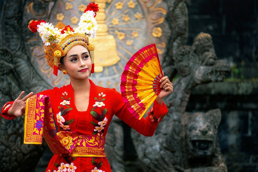 Balinese girl performing traditional dress with Hindu temple background.