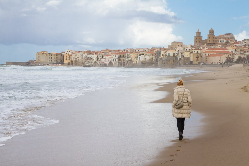 A woman walks the empty beach of Cefalu in the winter.