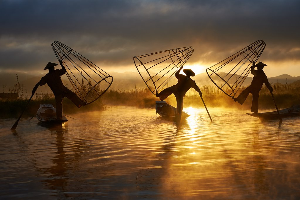 INLE, MYANMAR - NOVEMBER 28: Three fishermen perform the old traditional fishing method on the 28th of November 2018 in Myanmar at sunrise. Fishing with special shaped fishnets and the one legged rowing style is distinctive for Myanmar.
