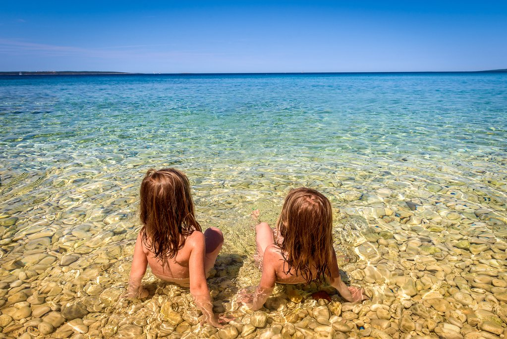 Twins playing in the shallows of the clear Adriatic Sea