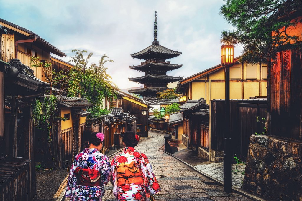 Two women wearing Kimonos walking through Kyoto