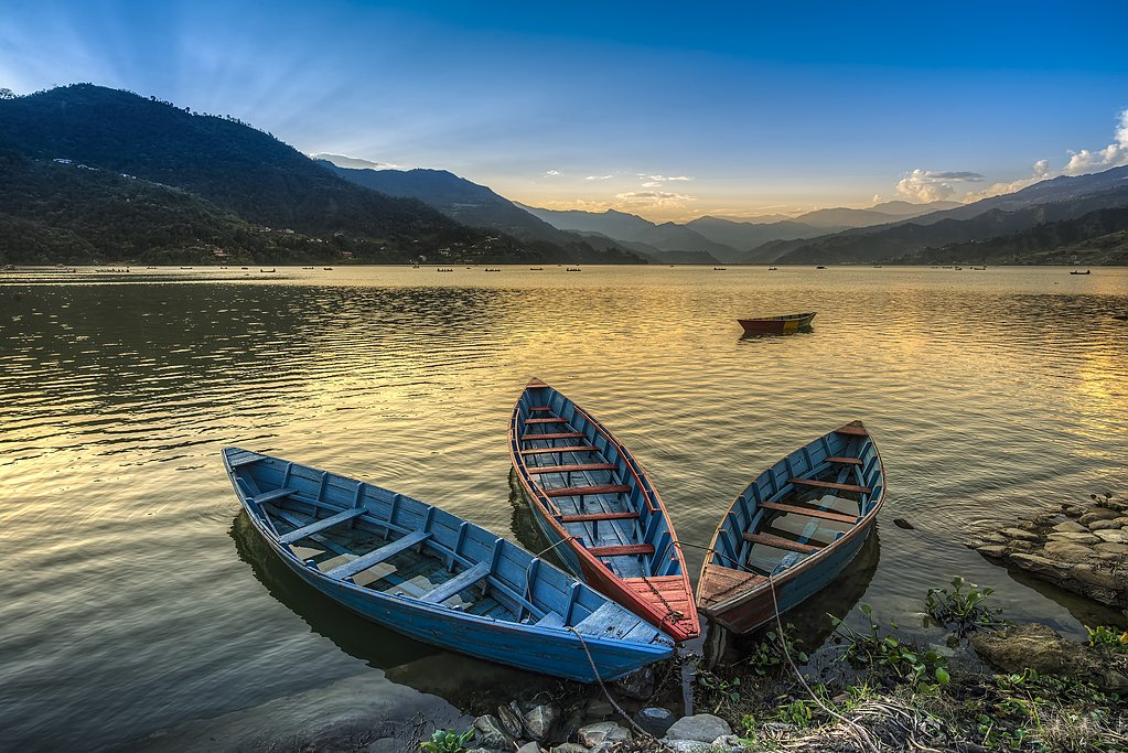 Boats for hire line the shore of Phewa Lake in Pokhara