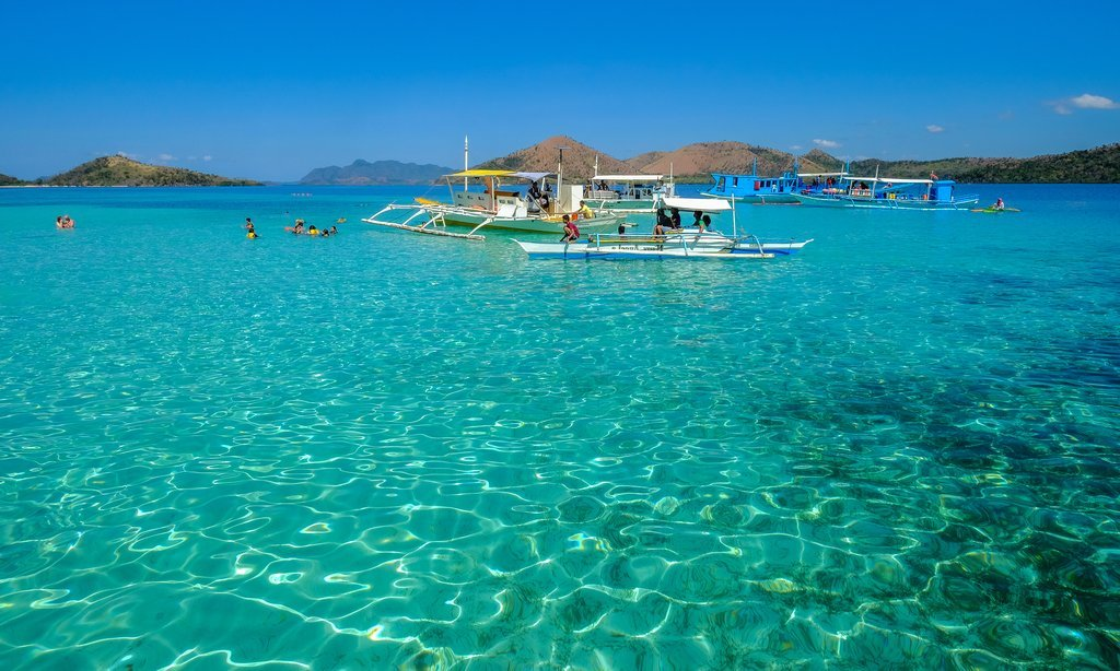 Modern banca boats carrying snorkeling enthusiasts near Coron Island