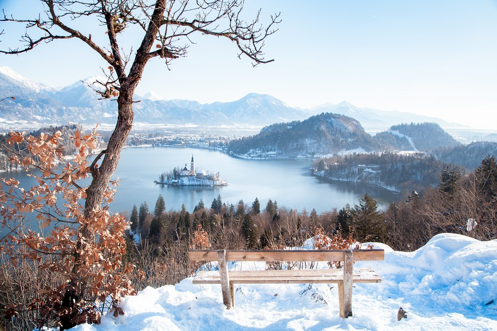 Slovenia's famous Lake Bled in winter with a view of the Julian Alps in the background