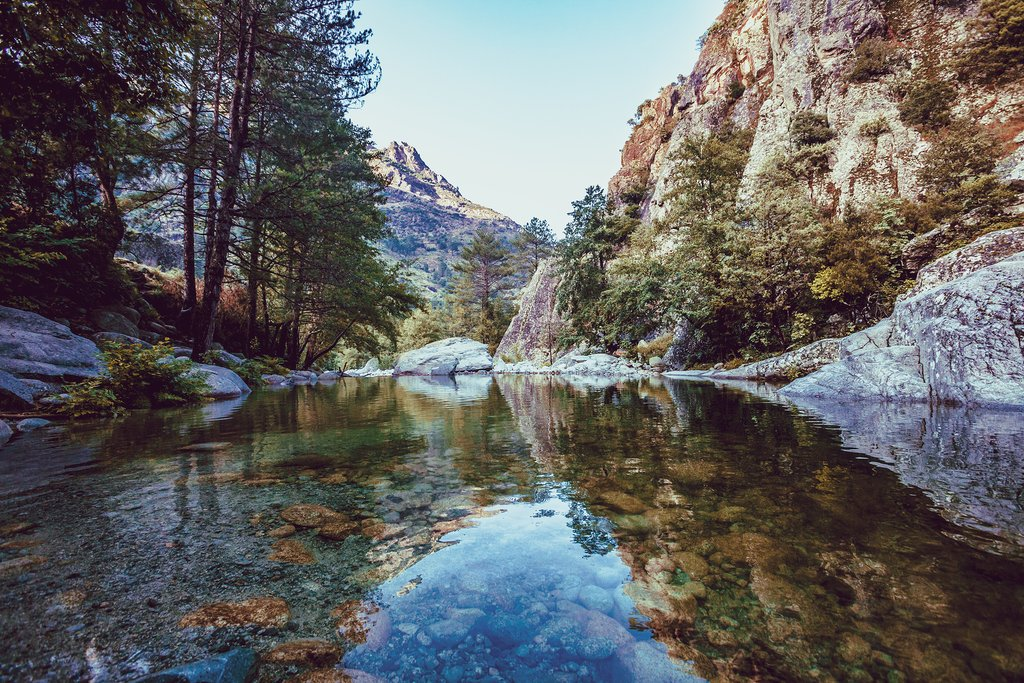 River with pebbles, mountains and picturesque forest on Corsica