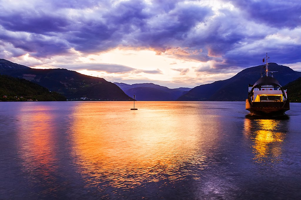 A sunset ferry cruises the Hardangerfjord