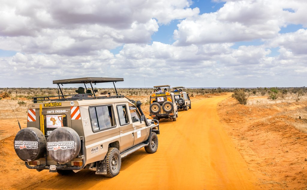 TSAVO EAST RESERVE, KENYA - OCTOBER 11, 2018: Safari cars with unindentified tourists on adventure trip in Tsavo East National Park, Kenya.