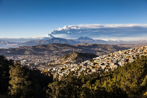 Quito in the foreground with an erupting Cotopaxi volcano in the distance.