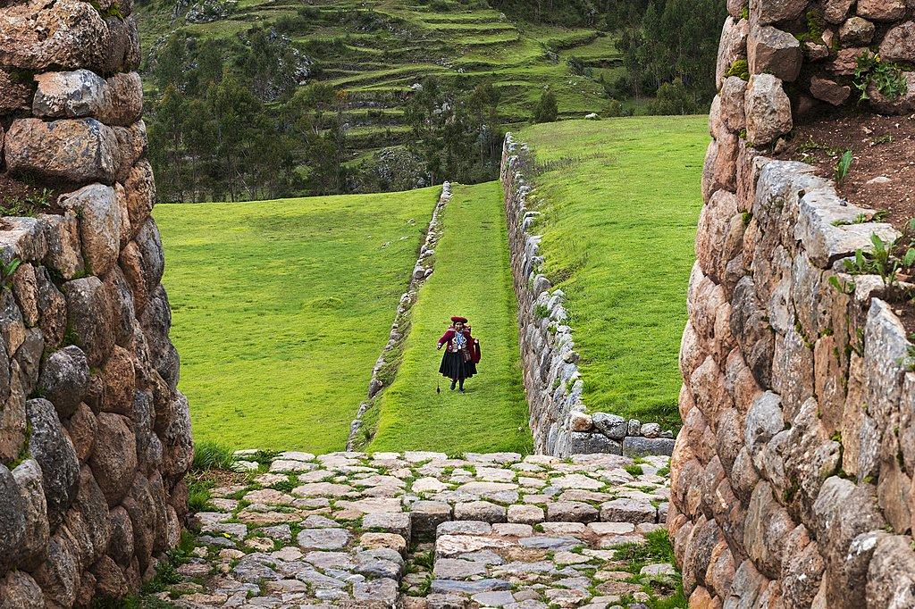 Peruvian woman walking through the Inca ruins of Chinchero