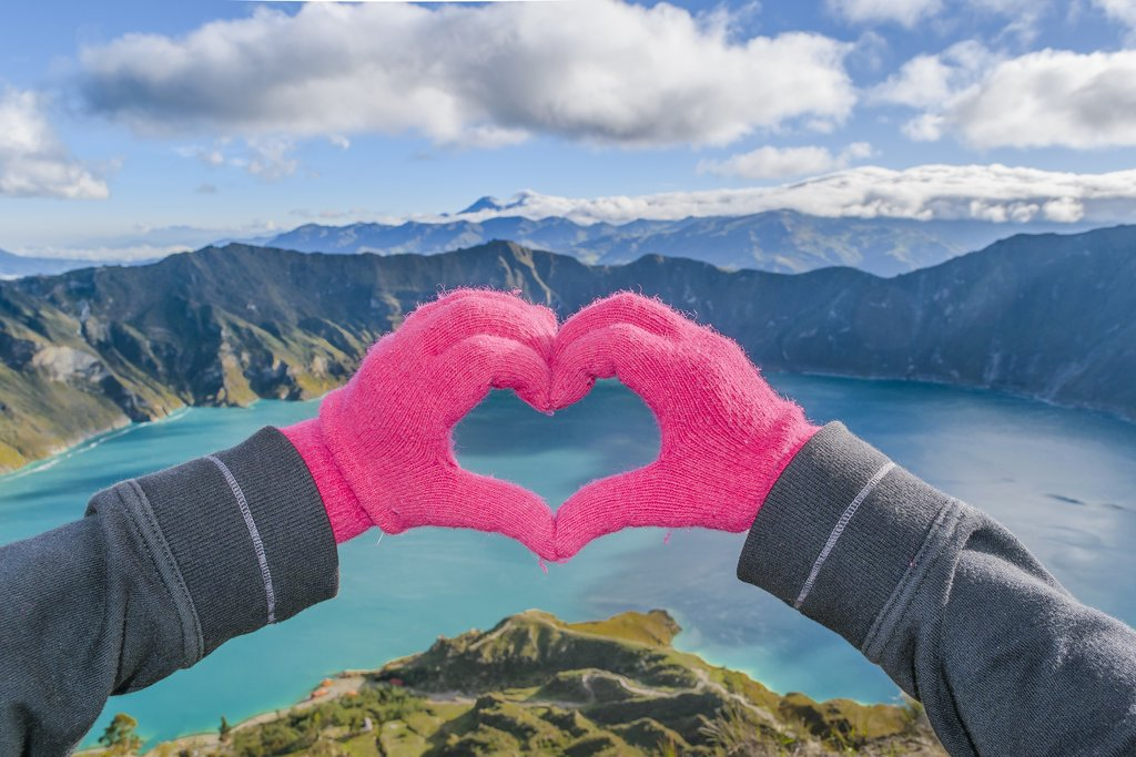 Hands forming a heart in front of Quilotoa lake
