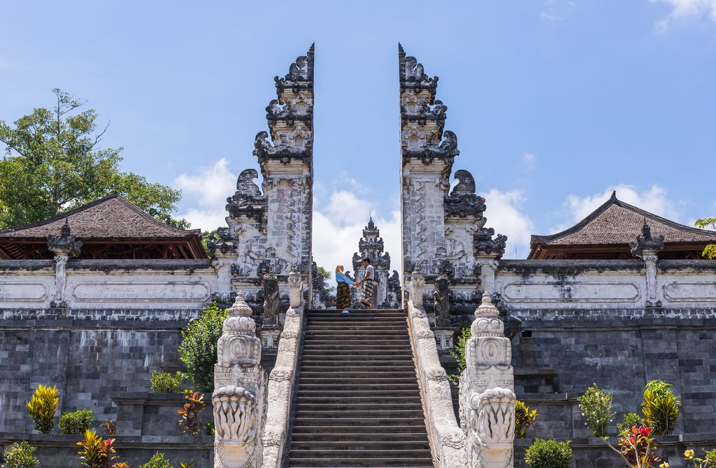 BALI, INDONESIA - SEPTEMBER 17, 2019: Couple at the entrance temple of Pura Penataran Agung Lempuyang. In Bali, Indonesia