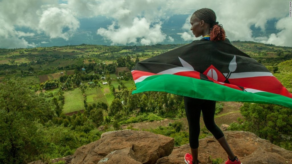 Marathoner Catherine Ndereba holds the Kenyan flag and looks out over Iten