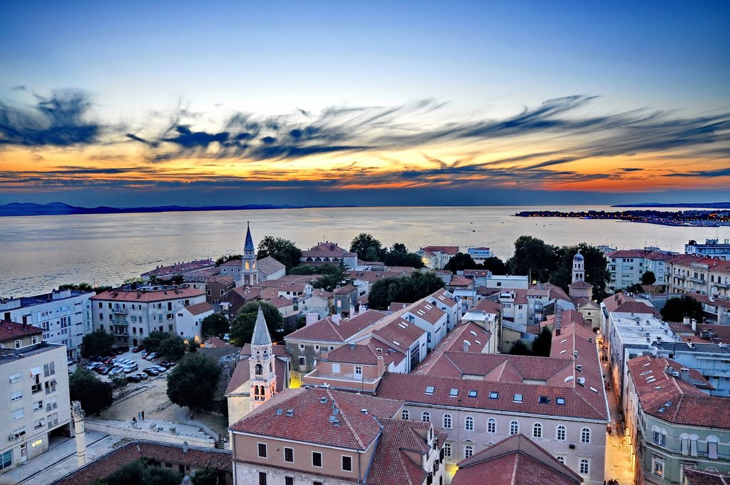 The sun sets over the Adriatic and Zadar's tiled rooftops