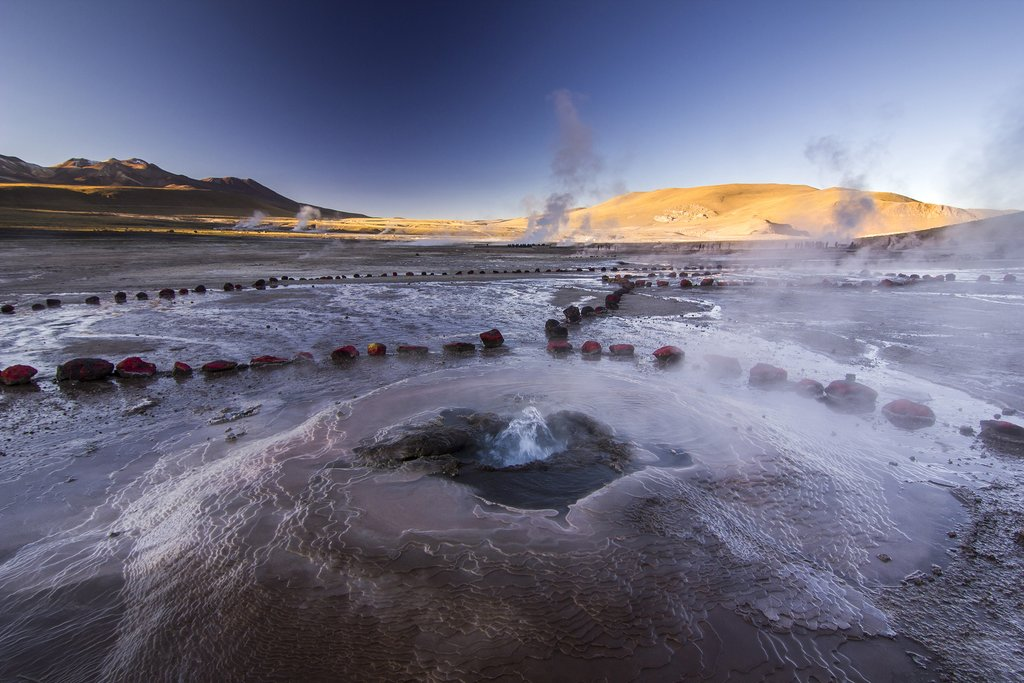 Steaming Tatio geysers erupting on a geothermal field