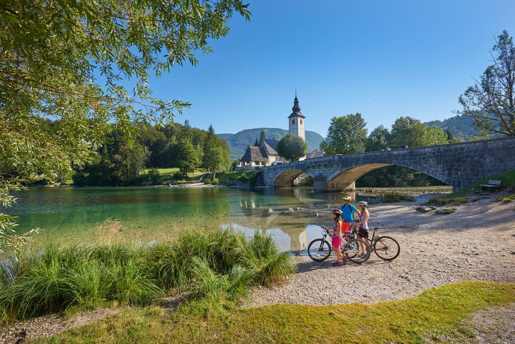 A cycling family enjoys the view of Bohinj Lake.