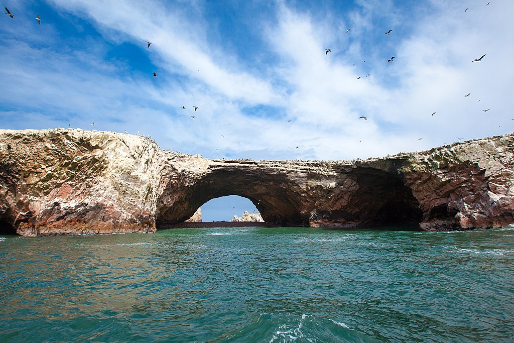 Birds flying over a natural arch in the Ballestas Islands