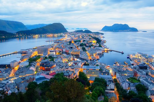 The pretty port city of Ålesund shines at dusk.