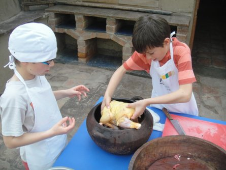 Kids baking a chicken according to a traditional Peruvian recipe
