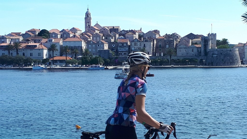 A cyclist looks to the Venetian-influenced city of Korčula Town