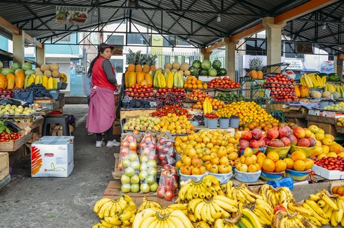 An Ecuadorian woman selling fruit in a marketplace