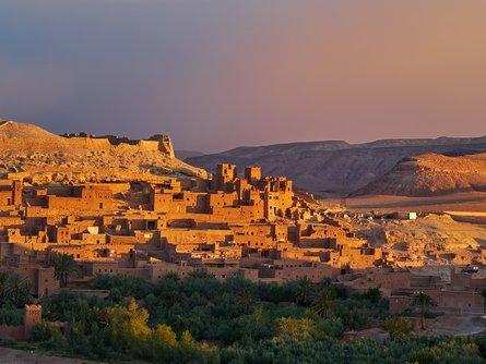 The sun sets over the Ouarzazate River and Aït Benhaddou