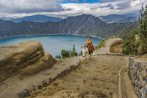 Boy riding a horse at Quilotoa lake in Ecuador